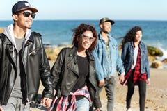 Groupe d'amis africains heureux marchant dehors à la plage Photographie stock libre de droits