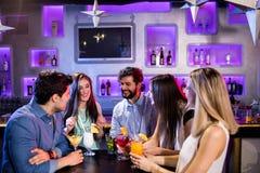 Groupe d'amis agissant l'un sur l'autre les uns avec les autres au compteur de barre tout en ayant le cocktail Image stock
