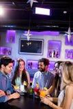 Groupe d'amis agissant l'un sur l'autre les uns avec les autres au compteur de barre tout en ayant le cocktail Photo stock