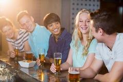Groupe d'amis agissant l'un sur l'autre les uns avec les autres tout en ayant la bière au compteur de barre Photographie stock libre de droits