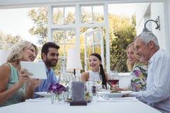 Groupe d'amis agissant l'un sur l'autre les uns avec les autres tout en ayant le repas ensemble Photos stock