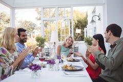 Groupe d'amis agissant l'un sur l'autre les uns avec les autres tout en ayant le repas ensemble Photo stock