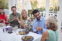 Groupe d'amis agissant l'un sur l'autre les uns avec les autres tout en ayant le repas ensemble Image stock