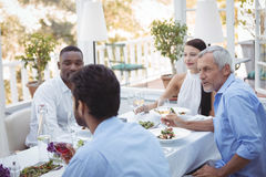 Groupe d'amis agissant l'un sur l'autre les uns avec les autres tout en prenant le déjeuner ensemble Photo libre de droits