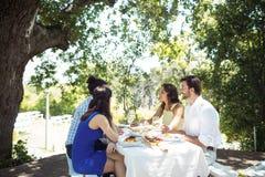 Groupe d'amis agissant l'un sur l'autre les uns avec les autres tout en prenant le déjeuner ensemble Photos libres de droits