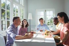 Groupe d'amis agissant l'un sur l'autre tout en ayant le repas Photo stock