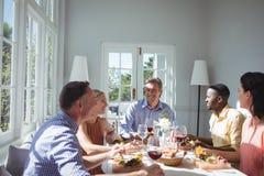 Groupe d'amis agissant l'un sur l'autre tout en ayant le repas Photographie stock libre de droits