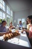 Groupe d'amis agissant l'un sur l'autre tout en prenant le petit déjeuner Images stock