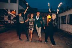 Groupe d'amis appréciant avec des cierges magiques sur la route Image libre de droits