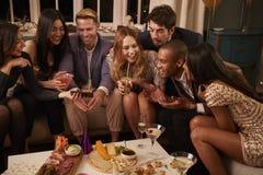 Groupe d'amis appréciant des boissons et des casse-croûte à la partie Images stock