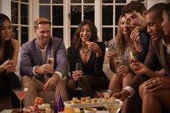 Groupe d'amis appréciant des boissons et des casse-croûte à la partie Photo stock