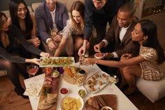 Groupe d'amis appréciant des boissons et des casse-croûte à la partie Photo libre de droits