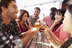 Groupe d'amis appréciant la boisson à la barre extérieure de dessus de toit photo stock