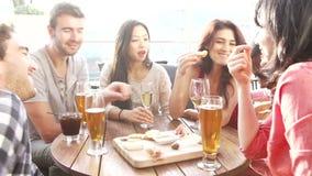 Groupe d'amis appréciant la boisson et le casse-croûte dans la barre de dessus de toit banque de vidéos