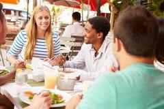 Groupe d'amis appréciant le déjeuner dans le restaurant extérieur Photographie stock libre de droits