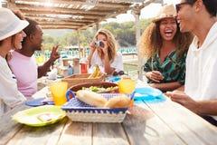Groupe d'amis appréciant le déjeuner et prenant des photographies Images stock
