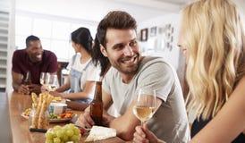 Groupe d'amis appréciant le dîner à la maison ensemble Image libre de droits