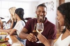 Groupe d'amis appréciant le dîner à la maison ensemble Image stock