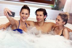 Groupe d'amis appréciant le jacuzzi dans la station thermale d'hôtel Image stock