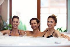 Groupe d'amis appréciant le jacuzzi dans la station thermale d'hôtel Images stock