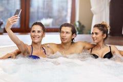 Groupe d'amis appréciant le jacuzzi dans la station thermale d'hôtel Photo libre de droits