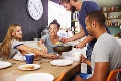 Groupe d'amis appréciant le petit déjeuner dans la cuisine ensemble Image libre de droits