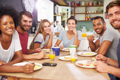 Groupe d'amis appréciant le petit déjeuner dans la cuisine ensemble Image stock