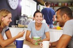 Groupe d'amis appréciant le petit déjeuner dans la cuisine ensemble Photographie stock