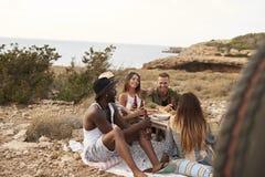 Groupe d'amis appréciant le pique-nique sur des falaises par la mer Photographie stock