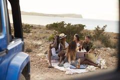 Groupe d'amis appréciant le pique-nique sur des falaises par la mer Photos libres de droits