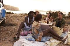 Groupe d'amis appréciant le pique-nique sur des falaises par la mer Images libres de droits