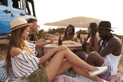 Groupe d'amis appréciant le pique-nique sur des falaises par la mer Photo stock