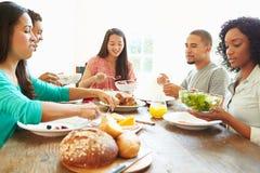Groupe d'amis appréciant le repas à la maison ensemble Image libre de droits