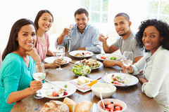 Groupe d'amis appréciant le repas à la maison ensemble Images stock