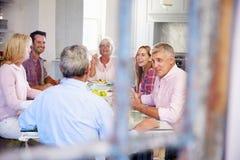 Groupe d'amis appréciant le repas à la maison ensemble Photo libre de droits