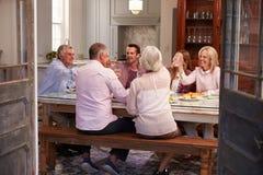 Groupe d'amis appréciant le repas à la maison ensemble Photographie stock