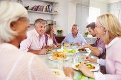 Groupe d'amis appréciant le repas à la maison ensemble Images libres de droits