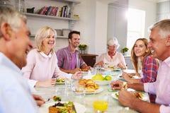 Groupe d'amis appréciant le repas à la maison ensemble Photos stock