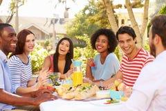Groupe d'amis appréciant le repas à la partie extérieure dans l'arrière cour Images libres de droits