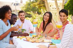 Groupe d'amis appréciant le repas à la partie extérieure dans l'arrière cour Photographie stock