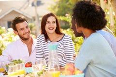 Groupe d'amis appréciant le repas à la partie extérieure dans l'arrière cour Image libre de droits