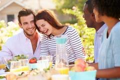 Groupe d'amis appréciant le repas à la partie extérieure dans l'arrière cour Images stock