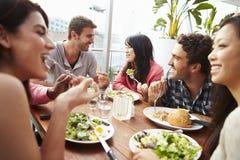 Groupe d'amis appréciant le repas au restaurant de dessus de toit Photo stock