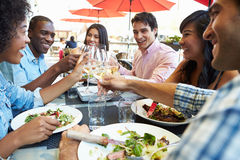 Groupe d'amis appréciant le repas au restaurant extérieur Photos stock