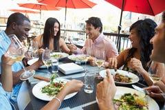 Groupe d'amis appréciant le repas au restaurant extérieur Photo libre de droits