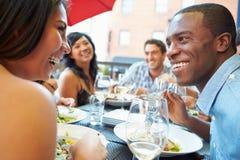 Groupe d'amis appréciant le repas au restaurant extérieur Images stock