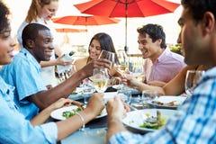 Groupe d'amis appréciant le repas au restaurant extérieur Image stock
