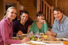 Groupe d'amis appréciant le repas dans le chalet alpestre Images stock