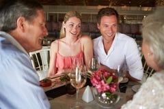 Groupe d'amis appréciant le repas dans le restaurant Image libre de droits