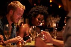 Groupe d'amis appréciant le repas dans le restaurant Photos libres de droits